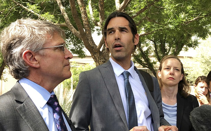 In this June 11, 2019 file photo Scott Warren, center, speaks outside federal court, in Tucson, Ariz., after a mistrial was declared in the federal case against him. The border activist will be retried after a jury was unable to reach a verdict on charges related to aiding migrants near Arizona's border with Mexico, U.S. prosecutors said Tuesday, July 2, 2019. (Astrid Galvan/AP, file)