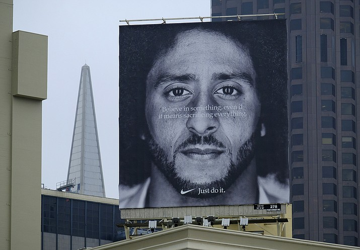 In this Sept. 5, 2018, file photo, a large billboard stands on top of a Nike store showing former San Francisco 49ers quarterback Colin Kaepernick, at Union Square in San Francisco. Nike is pulling a flag-themed tennis shoe after Kaepernick complained to the shoemaker, according to the Wall Street Journal. (Eric Risberg/AP, file)