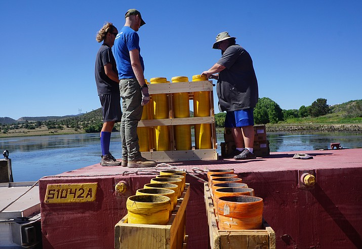 Southwest Fireworks employees Connor Ford, left, Doug Crumpton, center, and Kevin Massalone set up fireworks on a barge at Prescott's Watson Lake on Wednesday morning, July 3.  (Cindy Barks/Courier)