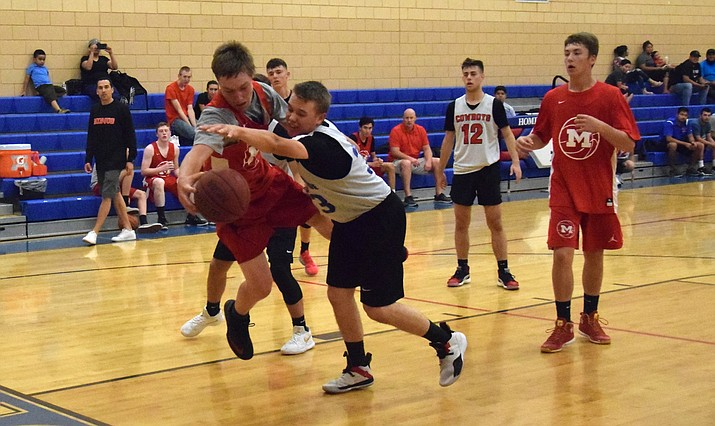 Mingus junior Zach Figy (red jersey) and Camp Verde senior Coke Bast (white jersey) battle for a rebound at the Cowboy Summer Shootout on Saturday night. VVN/James Kelley