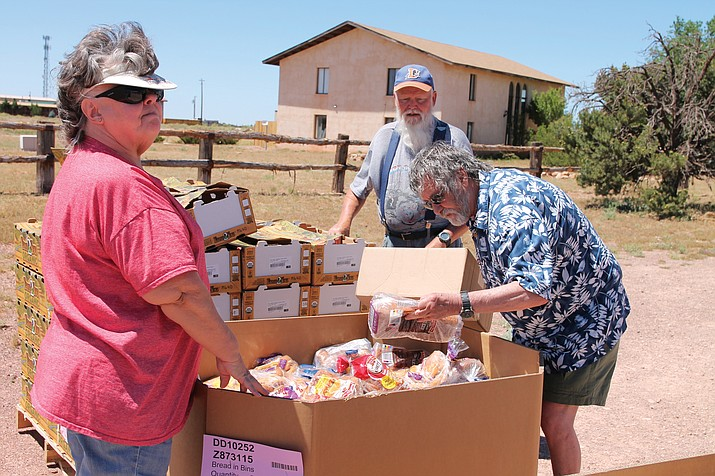 Sue Schumann and Steve Kanega help Valle residents sort through food items June 27. The food bank will be moving to Planes of Fame Air Museum next month. (Erin Ford/WGCN)