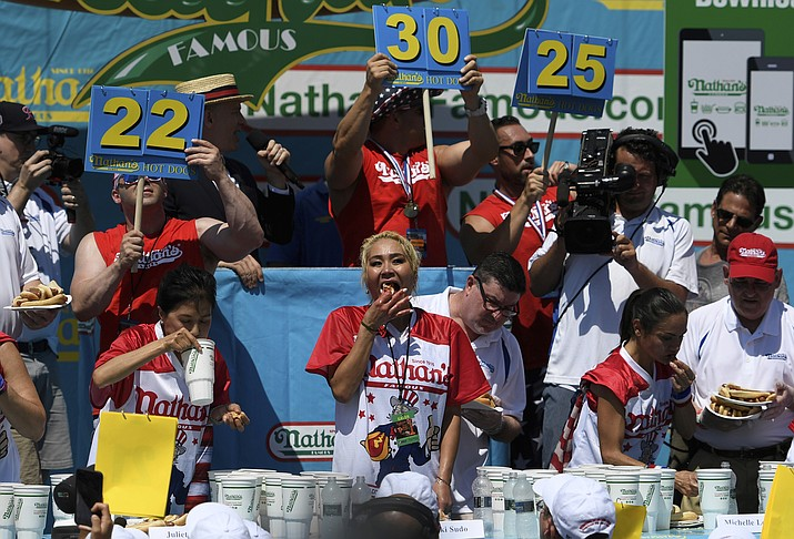 Juliet Lee, left, Miki Sudo, center, and Michelle Lesko, right, compete in the closing moments of the women's competition of the Nathan's Famous July Fourth hot dog eating contest, Thursday, July 4, 2019, in New York's Coney Island. (Sarah Stier/AP)