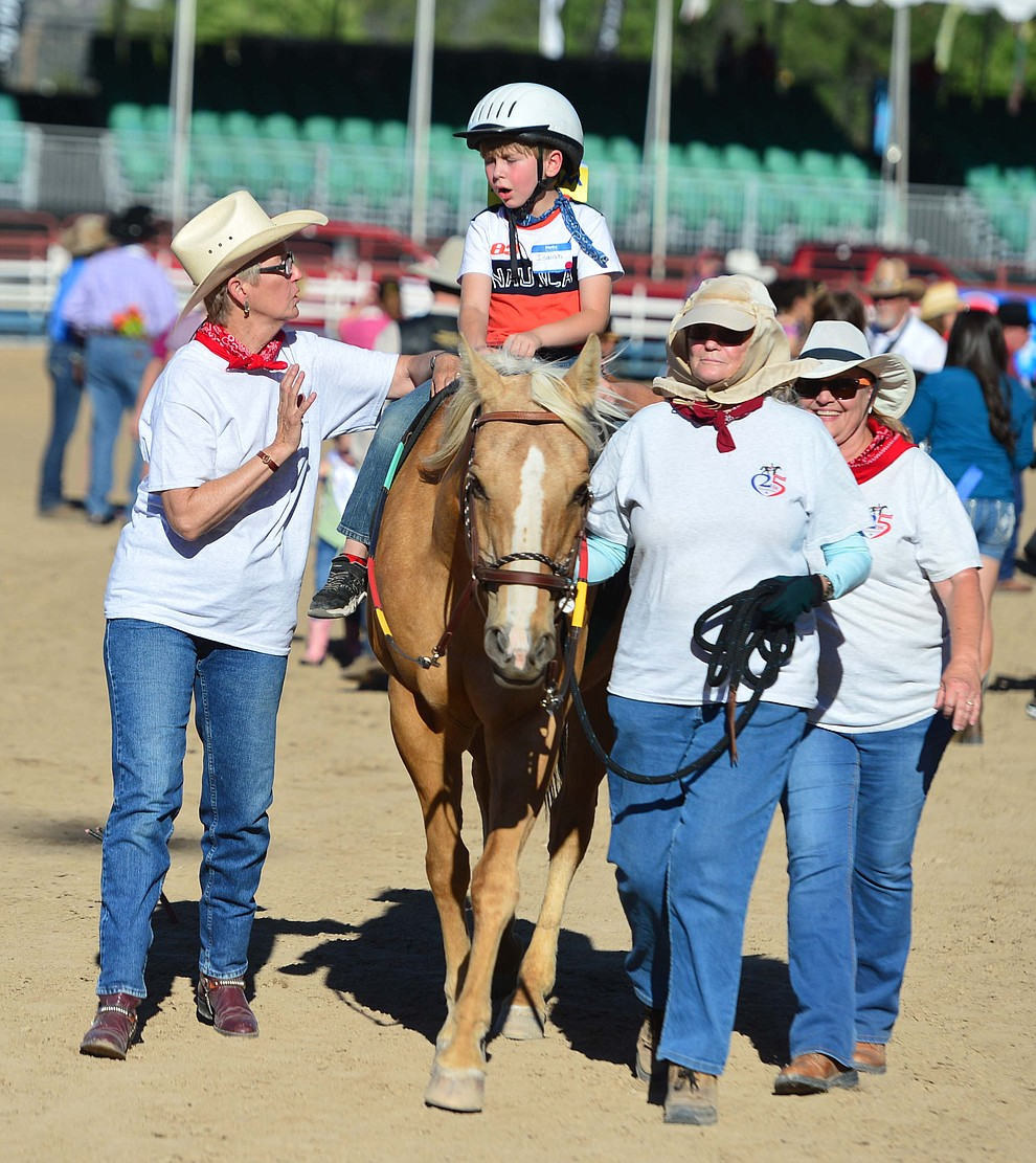 Seven-year old Isaiah Effenbeck rides with the Horses with Heart volunteers during the annual Happy Hearts Rodeo for Exceptional Children at the Prescott Frontier Days Rodeo Monday July 1, 2019.  (Les Stukenberg/Courier)