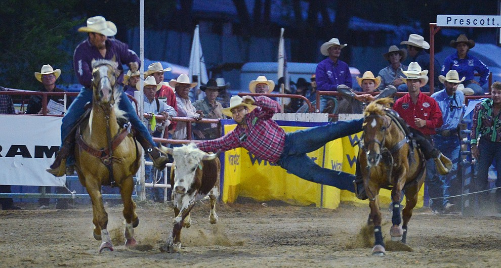 Denver Berry makes a long reach in the steer wrestling during the third performance of the Prescott Frontier Days Rodeo Wednesday July 3, 2019.  (Les Stukenberg/Courier)