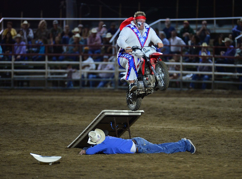 Rodeo Clown Justin Rumford makes a motorcycle jump during the third performance of the Prescott Frontier Days Rodeo Wednesday July 3, 2019.  (Les Stukenberg/Courier)