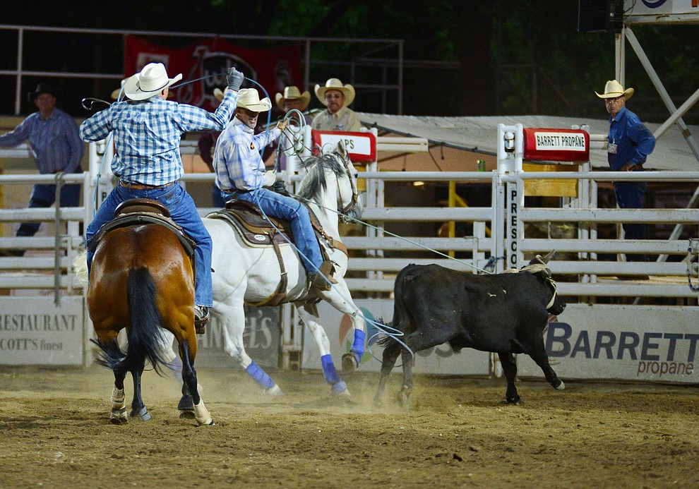Travis Bard and Clinton Teller make an 8.9 second run in the team roping during the third performance of the Prescott Frontier Days Rodeo Wednesday July 3, 2019.  (Les Stukenberg/Courier)