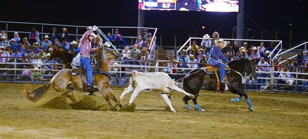 Tyler Worley and Jeff Flenniken make a 6.4 second run in the team roping during the third performance of the Prescott Frontier Days Rodeo Wednesday July 3, 2019.  (Les Stukenberg/Courier)