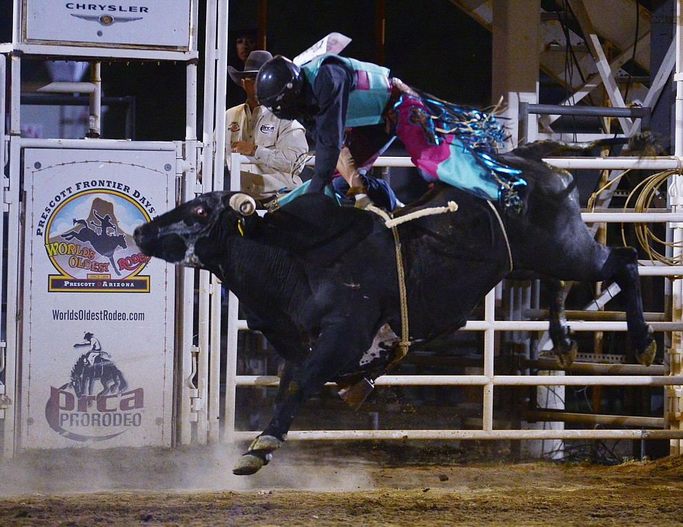 Paul Carrales gets air from Rustlers Roost in the bull riding during the third performance of the Prescott Frontier Days Rodeo Wednesday July 3, 2019.  (Les Stukenberg/Courier)