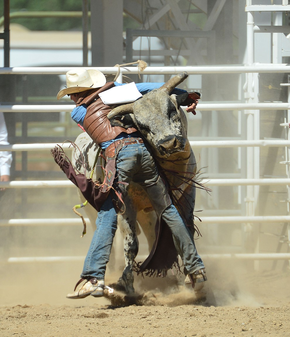Daniel Keeping gets a hornful from Last Cigarette in the bull riding during the fourth performance of the Prescott Frontier Days Rodeo Thursday July 4, 2019.  (Les Stukenberg/Courier)