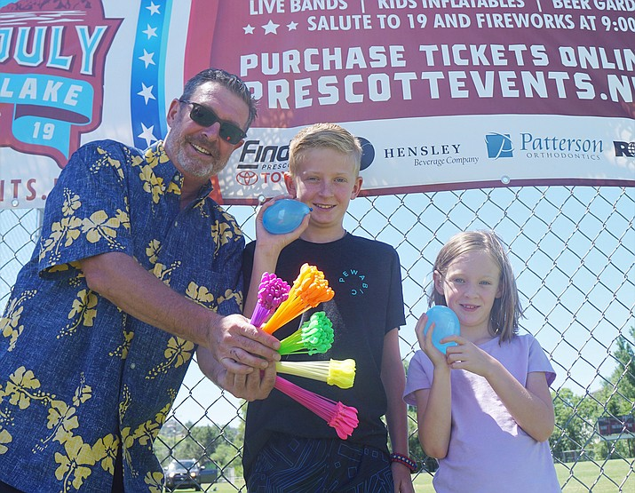 Steve Gottlieb, left, and his children, Garrett and Ava, check out the water balloon bunches that will be featured at the Water Wars event at the Prescott Mile High Middle School field on Saturday afternoon, July 6, 2019. (Cindy Barks/Courier)