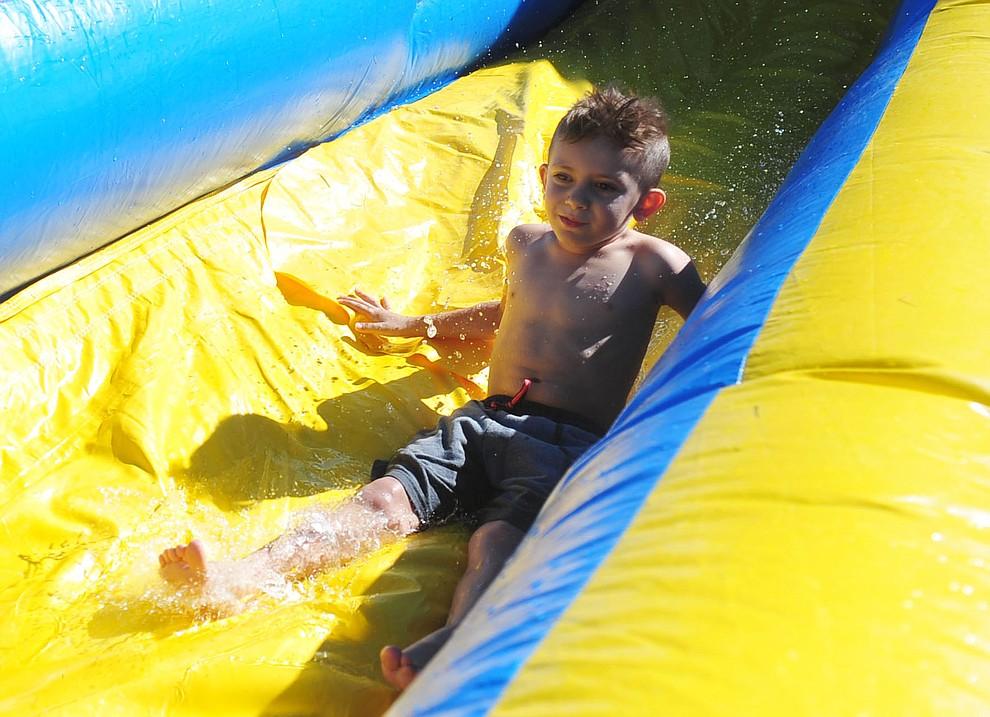 Tatum Podczerviensky, 6 of Prescott, enjoys a water slide at the City of Prescott's Watson Lake Fourth of July Celebration Thursday July 4, 2019.  (Les Stukenberg/Courier)