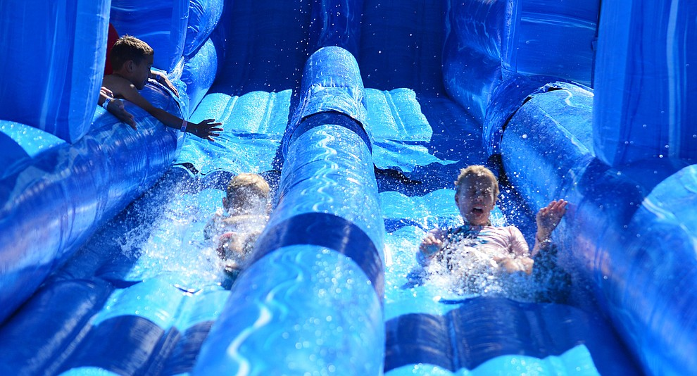 Kids enjoy the big water slides at the City of Prescott's Watson Lake Fourth of July Celebration Thursday July 4, 2019.  (Les Stukenberg/Courier)