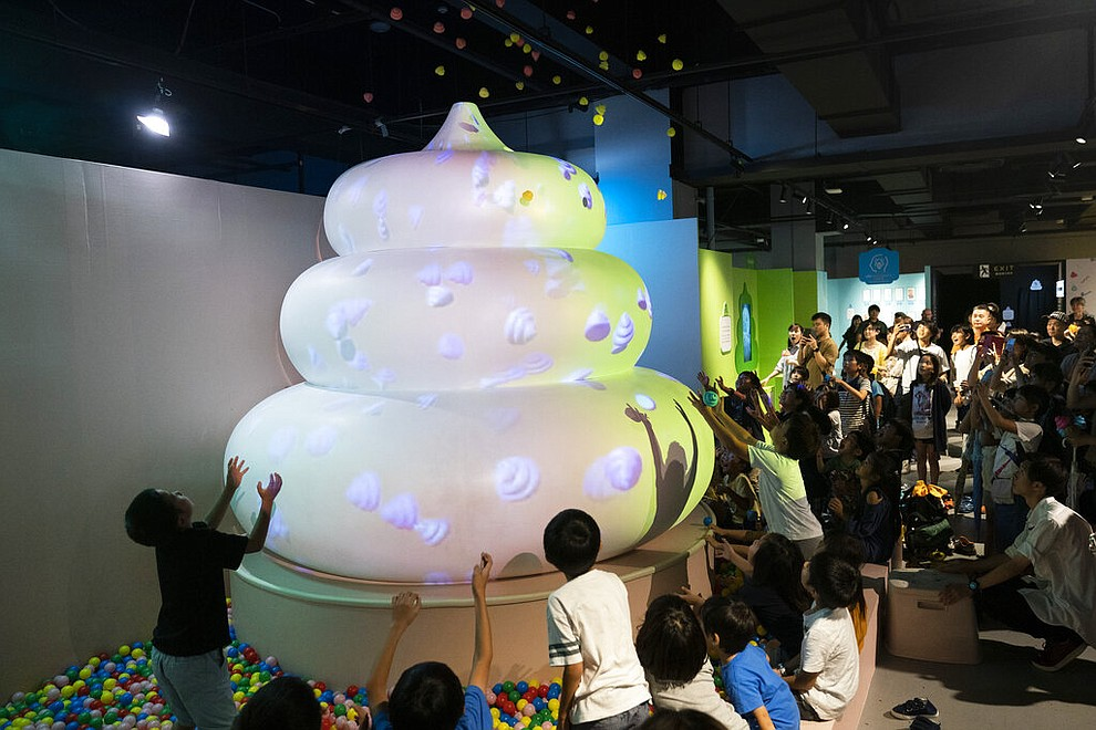 In this Monday, July 1, 2019, photo, a group of children try to catch small toy poops gushing from a giant poop-shaped inflatable at the Unko Museum in Yokohama, south of Tokyo. In a country known for its cult of cute, even poop is not an exception. A pop-up exhibition at the Unko Museum in the port city of Yokohama is all about unko, a Japanese word for poop. The poop installations there get their cutest makeovers. They come in the shape of soft cream, or cupcake toppings. (AP Photo/Jae C. Hong)