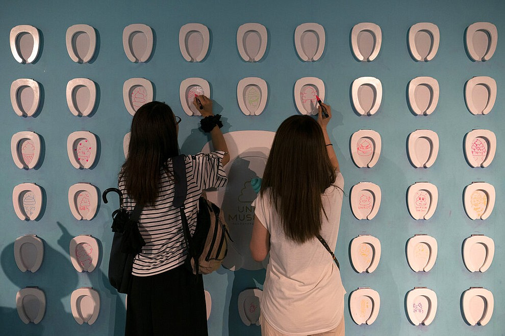 In this Tuesday, June 18, 2019, photo, two women draw on toilet-shaped boards at the Unko Museum in Yokohama, south of Tokyo. In a country known for its cult of cute, even poop is not an exception. A pop-up exhibition at the Unko Museum in the port city of Yokohama is all about unko, a Japanese word for poop. The poop installations there get their cutest makeovers. They come in the shape of soft cream, or cupcake toppings. (AP Photo/Jae C. Hong)