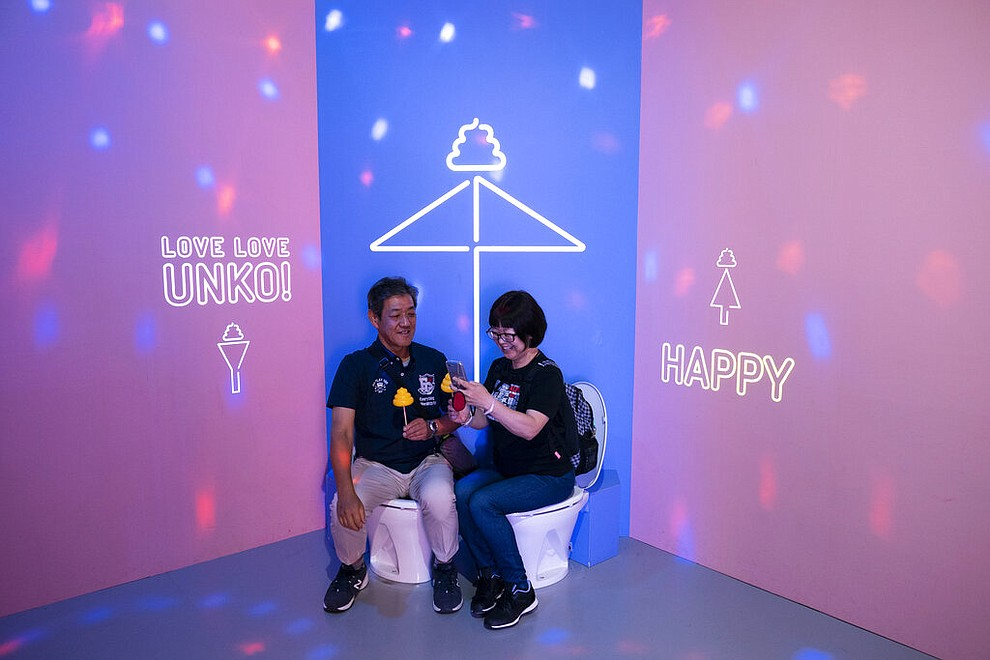 In this Tuesday, June 18, 2019, photo, a couple shares a light moment while sitting on toilet bowls at the Unko Museum in Yokohama, south of Tokyo. In a country known for its cult of cute, even poop is not an exception. A pop-up exhibition at the Unko Museum in the port city of Yokohama is all about unko, a Japanese word for poop. The poop installations there get their cutest makeovers. They come in the shape of soft cream, or cupcake toppings. (AP Photo/Jae C. Hong)