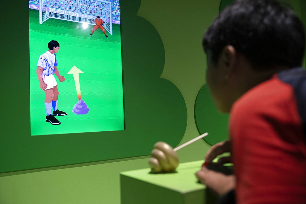 In this Monday, July 1, 2019, photo, a young boy plays a video game at the Unko Museum in Yokohama, south of Tokyo. In a country known for its cult of cute, even poop is not an exception. A pop-up exhibition at the Unko Museum in the port city of Yokohama is all about unko, a Japanese word for poop. The poop installations there get their cutest makeovers. They come in the shape of soft cream, or cupcake toppings. (AP Photo/Jae C. Hong)