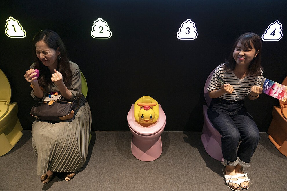 In this Tuesday, June 18, 2019, photo, two women jokingly motion to give a push while sitting on colorful toilet bowls at the Unko Museum in Yokohama, south of Tokyo. In a country known for its cult of cute, even poop is not an exception. A pop-up exhibition at the Unko Museum in the port city of Yokohama is all about unko, a Japanese word for poop. The poop installations there get their cutest makeovers. They come in the shape of soft cream, or cupcake toppings. (AP Photo/Jae C. Hong)