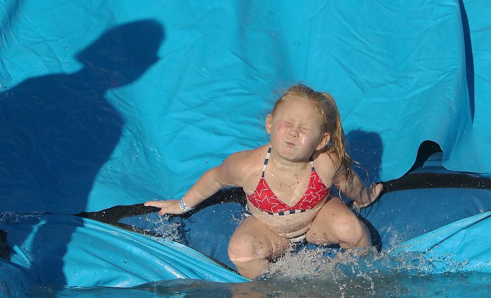 Four year old Aubrey Legler of Prescott enjoys the splash down slide at the Chino Valley July 4th Celebration.