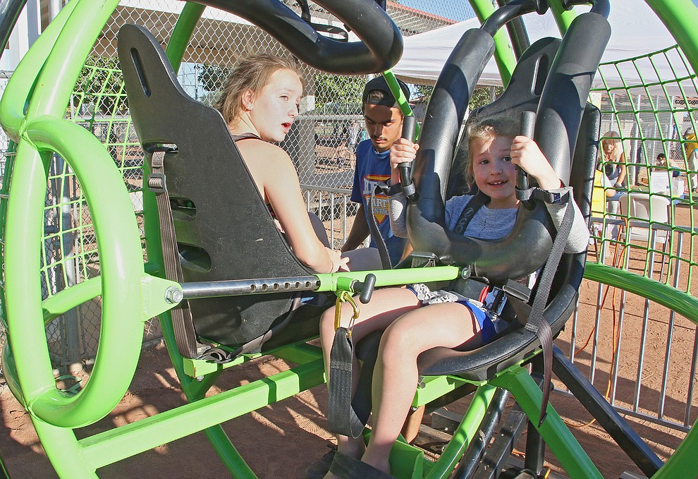 Evelyn James (6 yrs old, Right) and sister Bailey (Left)  get strapped in to enjoy the Human Gyroscope ride at the Town of Chin Valley July 4th Event.