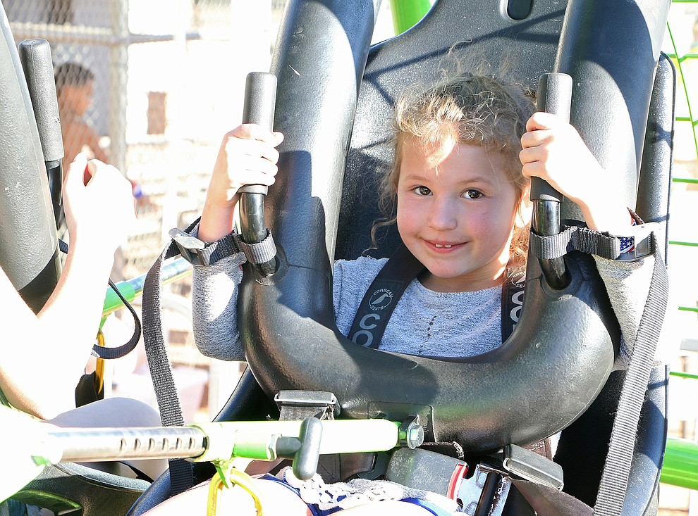 Evelyn James (6 yrs old) gets strapped in to enjoy the Human Gyroscope ride at the Town of Chin Valley July 4th Event.