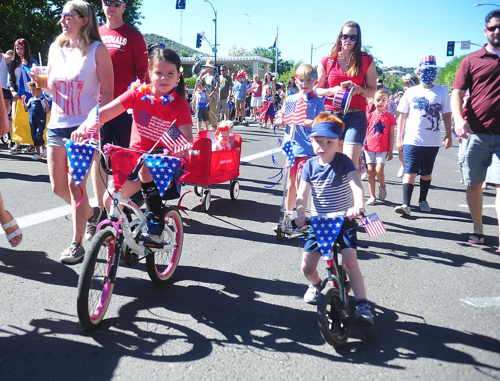 Children on bikes, scooters and in wagons ride during the 78th annual Kiwanis Kiddie Parade along Cortez Street in downtown Prescott Friday July 5, 2019.  (Les Stukenberg/Courier)