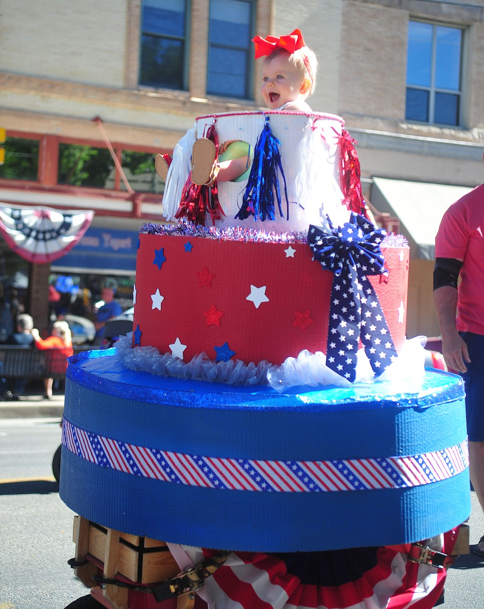 Ensley Smith is all smiles coming out of America's birthday cake during the 78th annual Kiwanis Kiddie Parade along Cortez Street in downtown Prescott Friday July 5, 2019.  (Les Stukenberg/Courier)