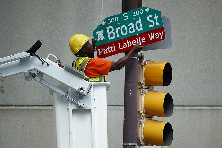 """A worker hangs a street sign before a ceremony honoring singer Patti LaBelle in Philadelphia. A stretch of Broad Street, between Locust and Spruce Streets, will be renamed """"Patti LaBelle Way."""" (AP Photo/Matt Slocum)"""