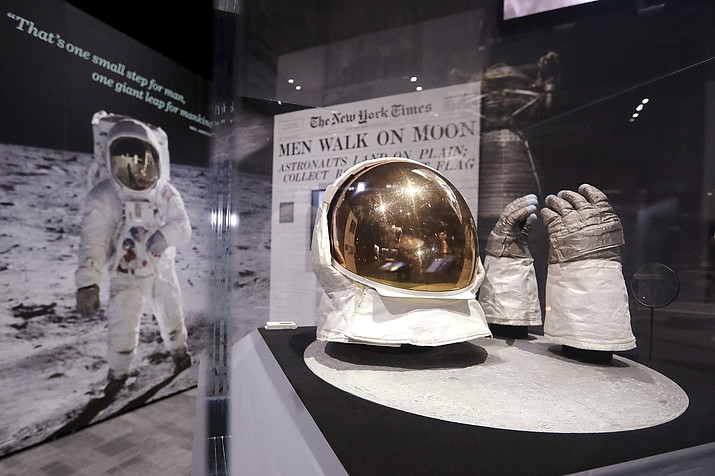 """Buzz Aldrin's outer visor and gloves worn while walking on the moon are displayed near a photo of Aldrin on April 11 at """"Destination Moon: The Apollo 11 Mission"""" exhibit at the Museum of Flight in Seattle. The exhibit celebrates the 50th anniversary of the U.S. manned moon landing on July 20, 1969. (Elaine Thompson/AP)"""