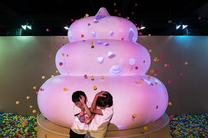 Two boys jokingly take cover as small toy poops gush from a giant poop-shaped inflatable at the Unko Museum in Yokohama, south of Tokyo.