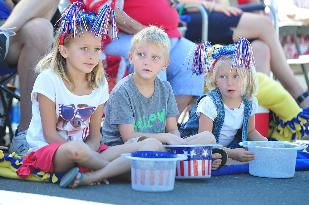 Allie, Ryan and Kate Crotts wait for the Prescott Frontier Days Rodeo Parade to begin through the streets of downtown Prescott Saturday July 6, 2019.  (Les Stukenberg/Courier)