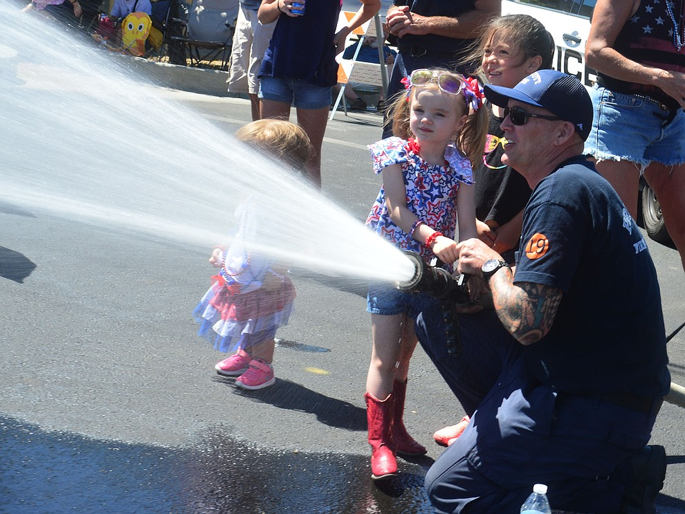 Jennifer Spence and Mase Smith help Prescott Fire Captain Matt Fifield cool down the crowd during the Prescott Frontier Days Rodeo Parade through the streets of downtown Prescott Saturday July 6, 2019.  (Les Stukenberg/Courier)