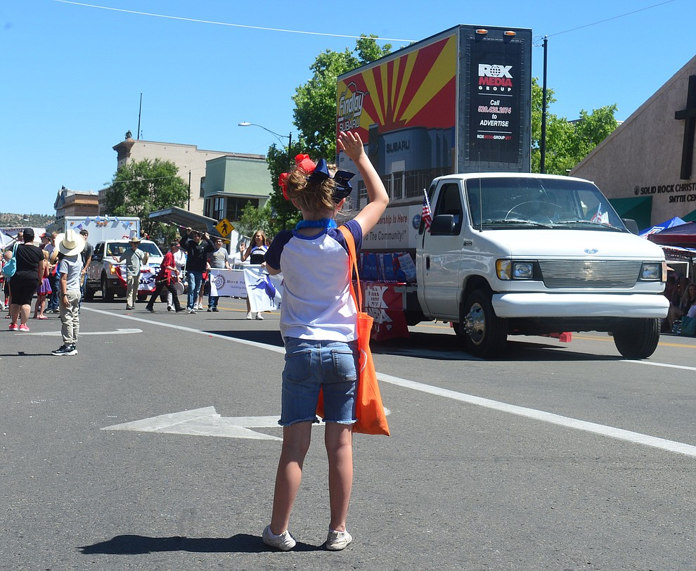 A young parade goer waves during the Prescott Frontier Days Rodeo Parade through the streets of downtown Prescott Saturday July 6, 2019.  (Les Stukenberg/Courier)