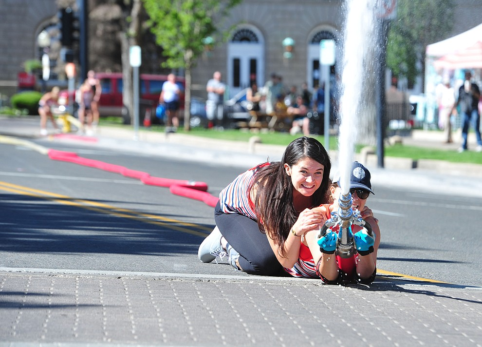 A team of wives and girlfriends of firefighters compete during the annual Hose Cart Races Sunday July 7, 2019 on Cortez Street in Prescott. The event has a history from the earliest days of the Prescott Fire Department when it was manned by volunteers. In the current version the competition has been going on for at least 70 years. (Les Stukenberg/Courier)
