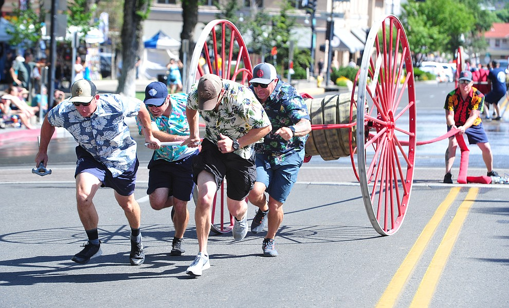 A team from Central Arizona Fire and Medical compete during the annual Hose Cart Races Sunday July 7, 2019 on Cortez Street in Prescott. The event has a history from the earliest days of the Prescott Fire Department when it was manned by volunteers. In the current version the competition has been going on for at least 70 years. (Les Stukenberg/Courier)