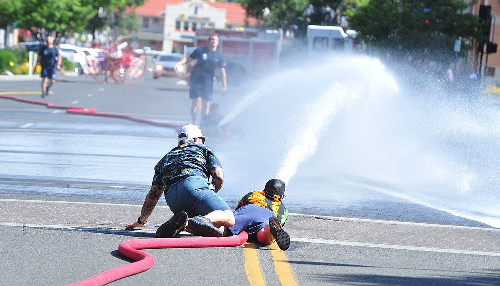 Trying to knock the cone over with a stream of water during the annual Hose Cart Races Sunday July 7, 2019 on Cortez Street in Prescott. The event has a history from the earliest days of the Prescott Fire Department when it was manned by volunteers. In the current version the competition has been going on for at least 70 years. (Les Stukenberg/Courier)