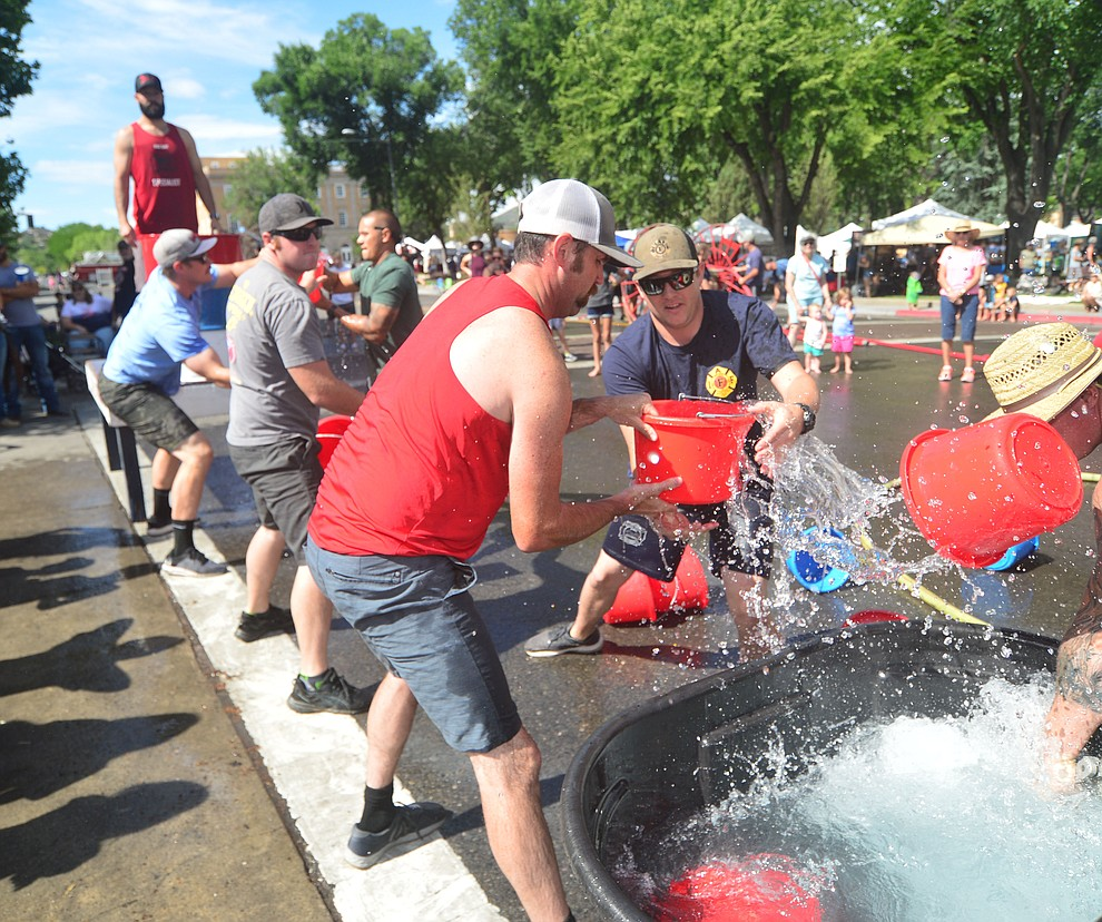 A team of Prescott firefighters compete in the bucket brigade during the annual Hose Cart Races Sunday July 7, 2019 on Cortez Street in Prescott. The event has a history from the earliest days of the Prescott Fire Department when it was manned by volunteers. In the current version the competition has been going on for at least 70 years. (Les Stukenberg/Courier)