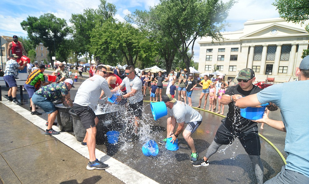 It's Central Arizona Fire versus Peoria Fire in the bucket brigade during the annual Hose Cart Races Sunday July 7, 2019 on Cortez Street in Prescott. The event has a history from the earliest days of the Prescott Fire Department when it was manned by volunteers. In the current version the competition has been going on for at least 70 years. (Les Stukenberg/Courier)