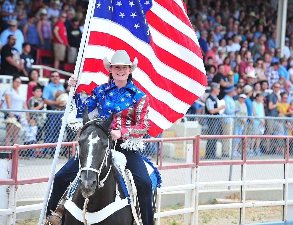 Sami Kilduff brings in the American Flag during the final performance of the Prescott Frontier Days Rodeo Sunday July 7, 2019.  (Les Stukenberg/Courier)