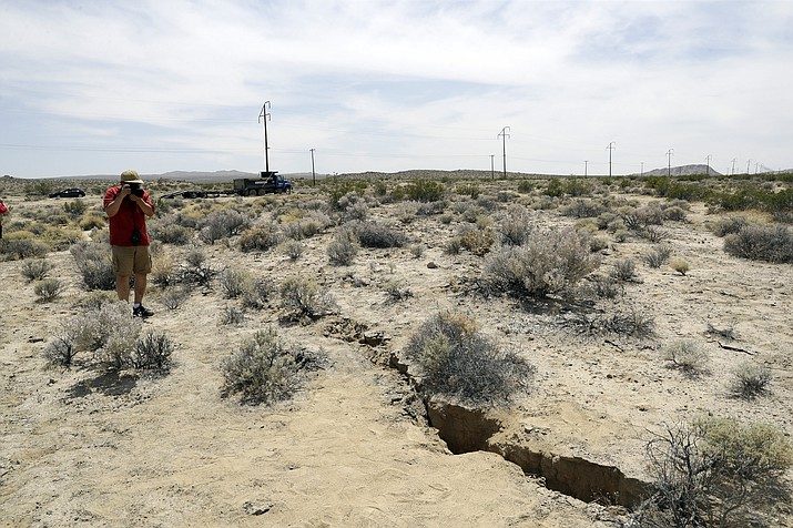 A visitor takes a photo of a crack on the ground following recent earthquakes Sunday, July 7, 2019, outside of Ridgecrest, Calif. (Marcio Jose Sanchez/AP)