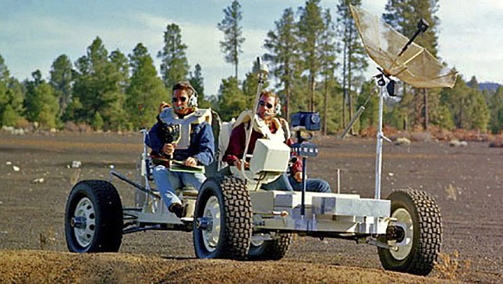 This undated photo provided by the U.S. Geological Survey Astrogeology Science Center shows Apollo 15 astronauts Jim Irwin, left, and Dave Scott driving a prototype of a lunar rover in a volcanic cinder field east of Flagstaff, Ariz. The rover, named Grover, now is on display at the science center. (U.S. Geological Survey Astrogeology Science Center)