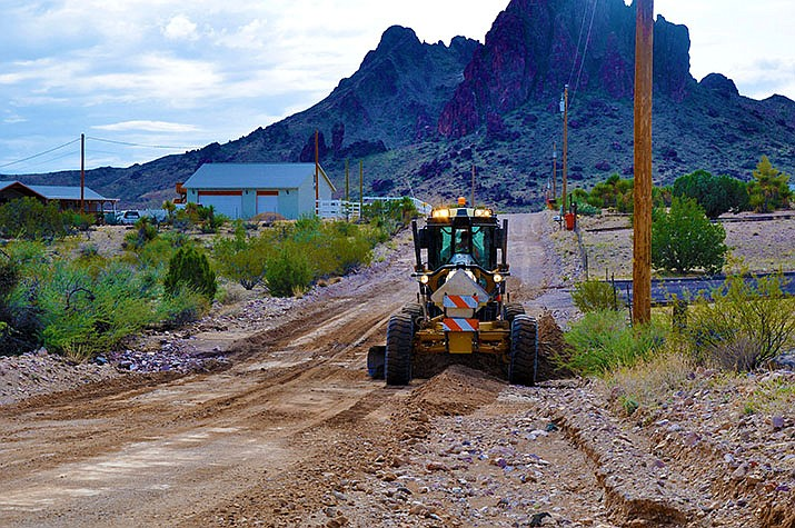 A Mohave County Road Department employee uses a road grader to smooth out South Dome Road in Golden Valley after a storm. (Photo by Butch Meriwether/For the Miner)