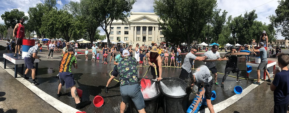 It's Central Arizona Fire versus Peoria Fire in the bucket brigade during the annual Hose Cart Races Sunday July 7, 2019 on Cortez Street in Prescott.  (Les Stukenberg/Courier)