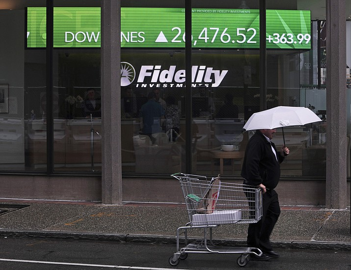 In this June 18, 2019, photo a man pulls a grocery cart as he walks in the rain past the stock ticker scroll board, showing a strong daily gain in the Dow Jones, outside Fidelity Investments in the Financial District of Boston. According to a survey by The Associated Press-NORC Center for Public Affairs Research, Americans are generally satisfied with their personal finances, but many lack confidence in their ability to afford retirement, an emergency expense or even their daily living costs (Charles Krupa/AP)