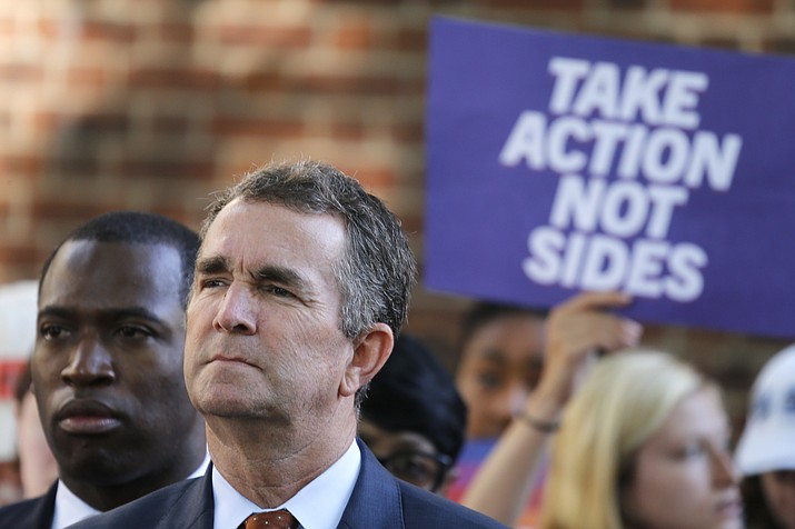 Virginia Gov. Ralph Northam, right, listens to speakers along with Richmond Mayor Levar Stoney, left, during a rally at the State Capitol in Richmond, Va., Tuesday, July 9, 2019. Governor Northam called a special session of the General Assembly to consider gun legislation in light of the Virginia Beach Shootings. (Steve Helber/AP)