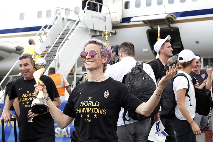 United States women's soccer team member Megan Rapinoe holds the Women's World Cup trophy after arriving with teammates at Newark Liberty International Airport, Monday, July 8, 2019, in Newark, N.J. (Kathy Willens/AP)