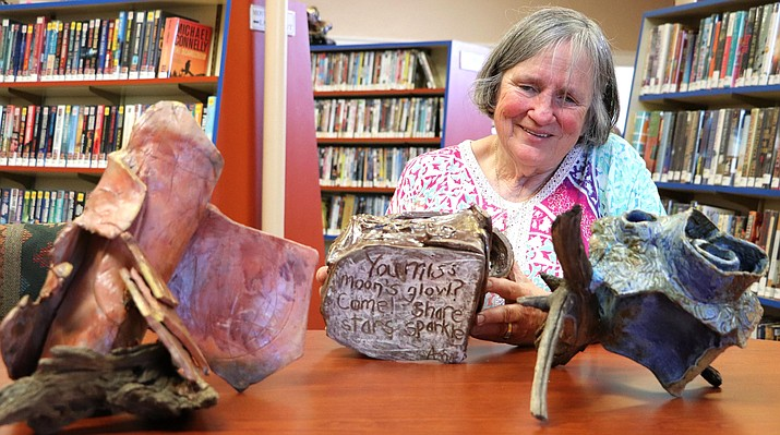 "Ann Metlay, Clarkdale artist-poet-author, shows the hidden poetry inscribed on one of her ceramic sculptures displayed in the Art in the Clark: ""Expressions in Clarkdale"" exhibition, running now through August 30th at Clark Memorial Library. (Photo courtesy David Perrell)"