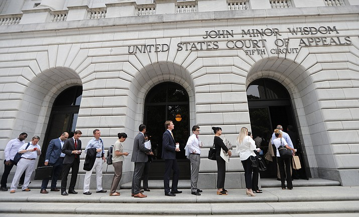 People wait in line to enter the 5th Circuit Court of Appeals to sit in overflow rooms to hear arguments in New Orleans, Tuesday, July 9, 2019. The appeals court will hear arguments today on whether Congress effectively invalidated former President Barack Obama's entire signature health care law when it zeroed out the tax imposed on those who chose not to buy insurance. A Texas judge in December ruled it was invalid, setting off an appeal by states who support the law. (Gerald Herbert/AP)