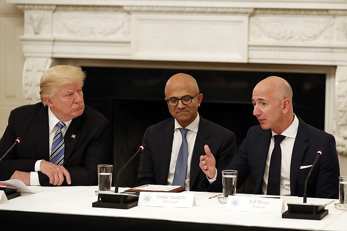 In this June 19, 2017, file photo President Donald Trump, left, and Satya Nadella, Chief Executive Officer of Microsoft, center, listen as Jeff Bezos, Chief Executive Officer of Amazon, speaks during an American Technology Council roundtable in the State Dinning Room of the White House in Washington. Amazon and Microsoft are battling for a $10 billion opportunity to build the U.S. military its first war cloud. (Alex Brandon/AP file)