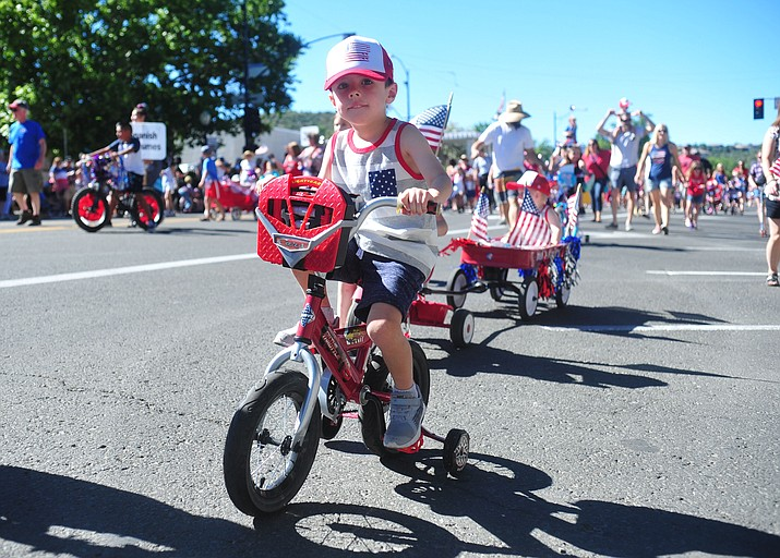 Children on bikes, scooters and in wagons ride during the 78th annual Kiwanis Kiddie Parade along Cortez Street in downtown Prescott on Friday July 5, 2019. (Les Stukenberg/Courier)