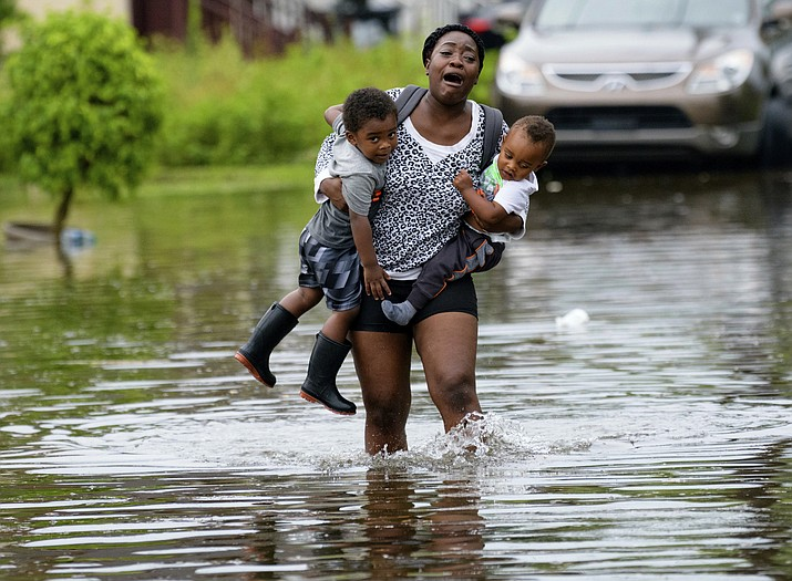 Terrian Jones reacts as she feels something moving in the water at her feet as she carries Drew and Chance Furlough to their mother on Belfast Street in New Orleans during flooding from a storm in the Gulf Mexico that dumped lots of rain Wednesday, July 10, 2019. (Matthew Hinton/AP)